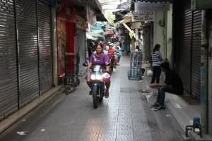 Rollerfahrer in einer Seitenstraße in China Town Bangkok