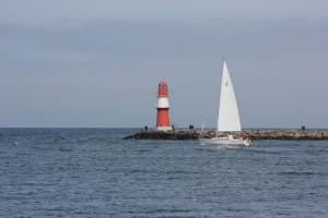 Segelboot am Molenfeuer Warnemünde an der Ostmole